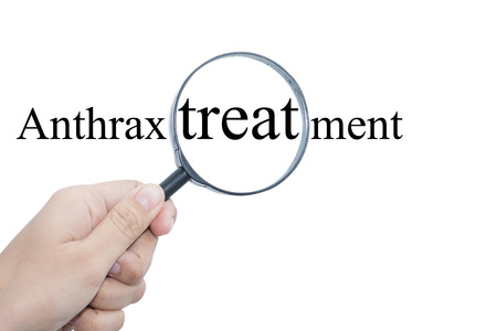 anthrax: Hand Showing Anthrax treatment Word Through Magnifying Glass  Stock Photo