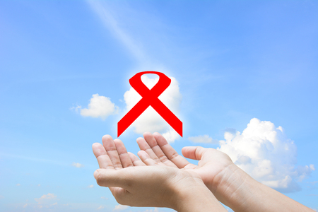 Man hands forming a heart with his hands and a red ribbon for the fight against AIDS  photo