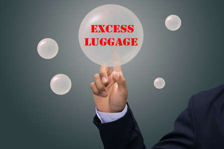 excess: business man writing EXCESS LUGGAGE concept Stock Photo