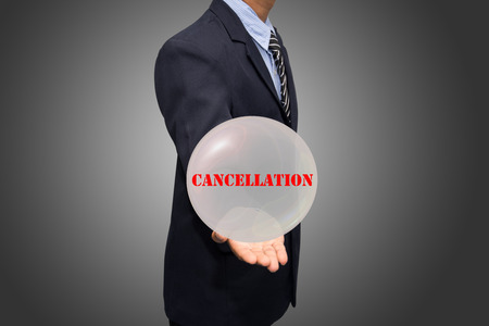 cancellation: business man writing CANCELLATION concept