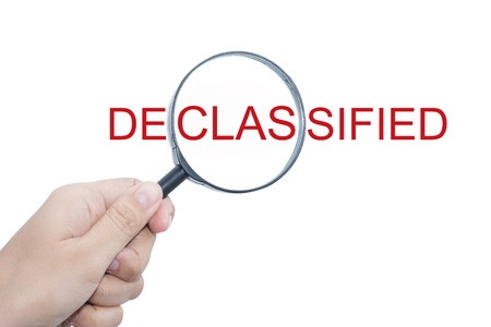 unrestricted: Hand Showing DECLASSIFIED Word Through Magnifying Glass Stock Photo