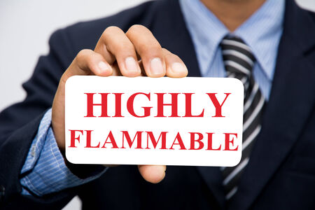 combustible: Businessman hand holding HIGHLY FLAMMABLE concept