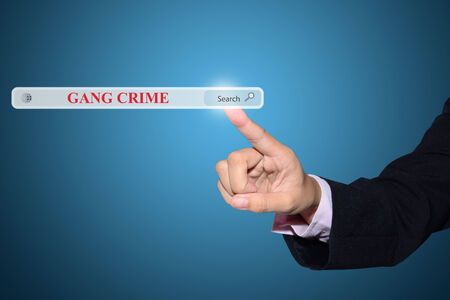 antisocial: Business and technology, searching system and internet concept - male hand pressing Search GANG CRIME button.