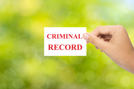 criminal activity: Hand holding a paper CRIMINAL RECORD on green background Stock Photo