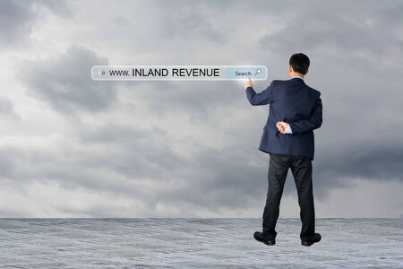 inland: Businessman hand pointing INLAND REVENUE Stock Photo
