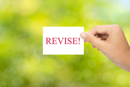 alterations: Hand holding a paper REVISE! on green background