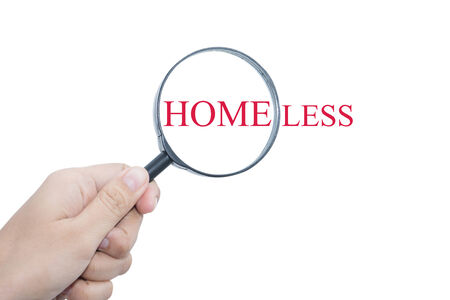 begging: Hand Showing HOMELESS Word Through Magnifying Glass Stock Photo