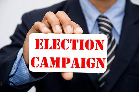 voters: Businessman hand holding ELECTION CAMPAIGN concept