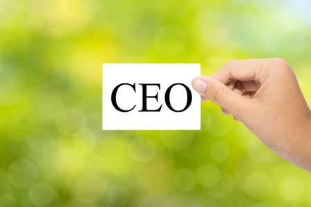 chief executive officers: Hand holding a paper CEO on green background Stock Photo