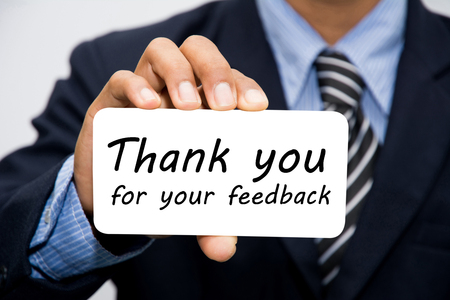 reviewing: Businessman hand holding Thank you for your feedback concept Stock Photo