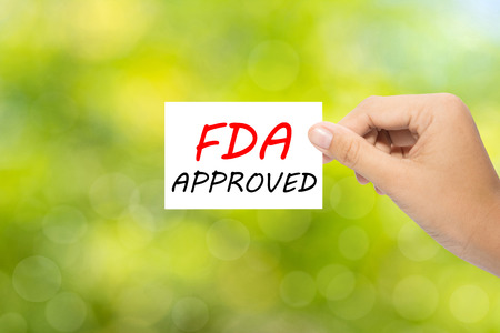fda: Hand holding a paper FDA APPROVED on green background
