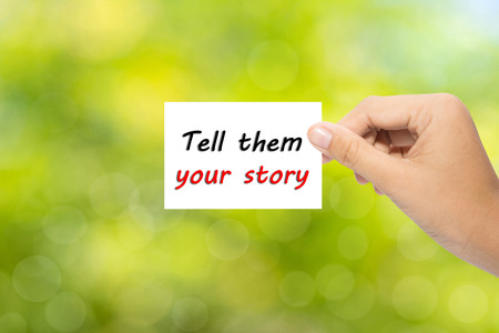 Hand holding a paper Tell them your story on green background