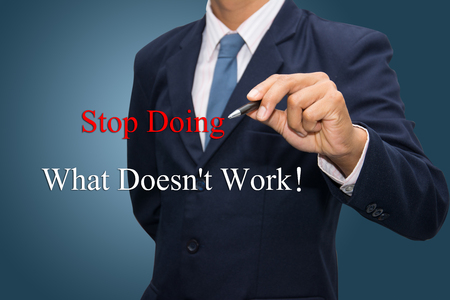 waste: Business man hand write Stop Doing What Doesnt Work