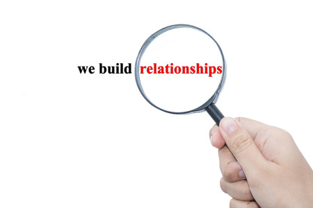 Hand Showing we build relationships Word Through Magnifying Glass Standard-Bild