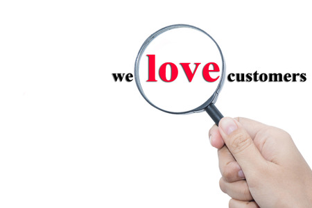 Hand Showing we love customers Word Through Magnifying Glass