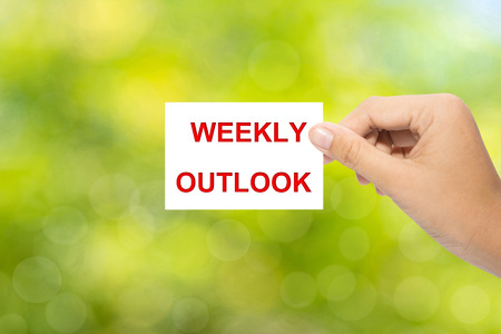 outlook: Hand holding a paper WEEKLY OUTLOOK on green background Stock Photo