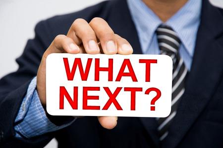 Businessman hand holding WHAT NEXT? concept
