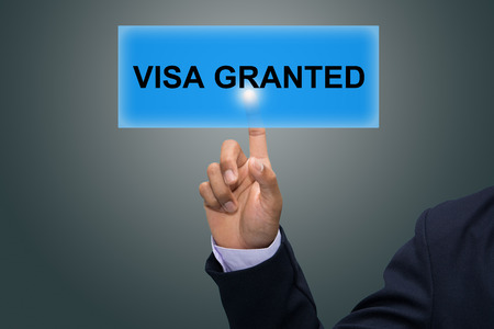 granted: Businessman hand pointing VISA GRANTED Stock Photo