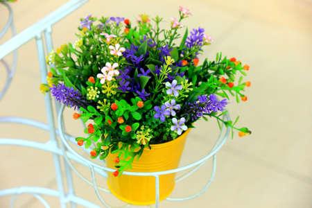 Plastic flowers in Yellow Pot Stock Photo