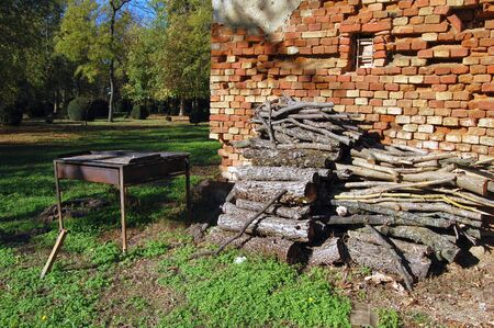 dilapidated wall: Firewood stacked next to the dilapidated wall. Logs are stored for fuel and to work with grill located next to the wall. Stock Photo