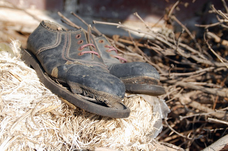Old decomposing shoes that remind one of the famous actor Charlie Chaplin. Stock Photo