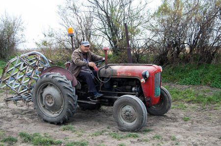 cramps: Farmer on old tractor cramps stubble on his field in Serbia. Preparing the country for the autumn plowing.