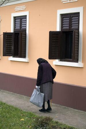slowly: Abuela Mayor comenzó a caminar por la calle a la tienda.