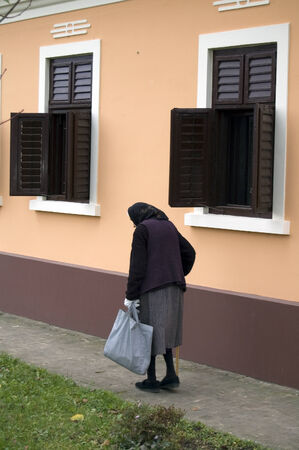 slowly: Older grandmother started walking in the street to the store.