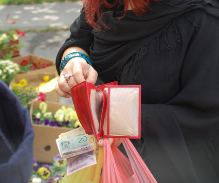 dinar: The young woman at the market pays in cash just bought flowers. Stock Photo