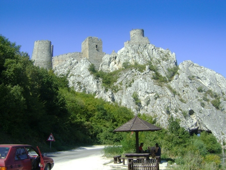 stock photography: Golubac fortress at the entrance of the river Danube in the Iron Gates Gorge. The road passes beneath the fortress through the tunnel.
