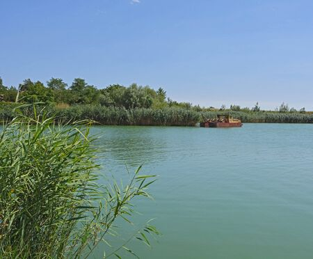 dredging: Lake with clear water, reeds and a dredging boat. Stock Photo