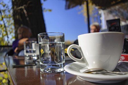 stock photography: Tavern table outdoors with a glass and coffee cup.