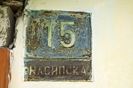 number 15: Old house with the number 15 and the name of the street. Stock Photo
