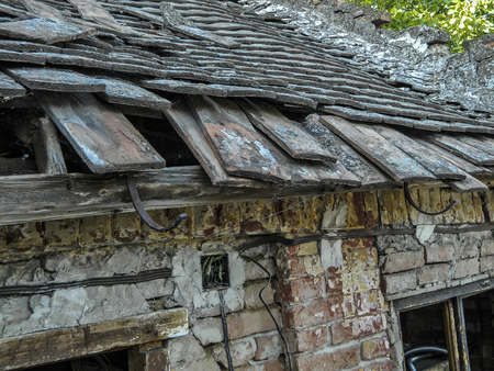 damaged roof: A decrepit old house with a damaged and devastated roof and tiles.