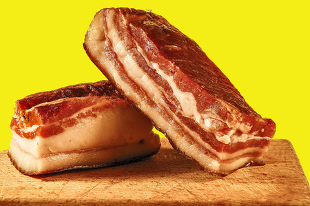 meaty: Two pieces of meaty smoked bacon home on a kitchen cutting board. Stock Photo