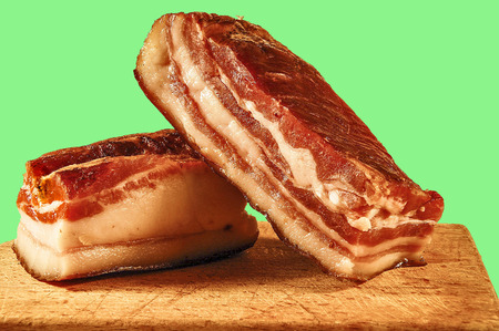 stock photography: Two pieces of meaty smoked bacon home on a kitchen cutting board. Stock Photo