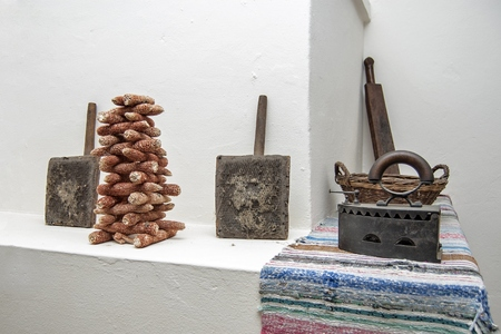 floor cloth: Old tools, iron and fuel for the winter are on the stove.