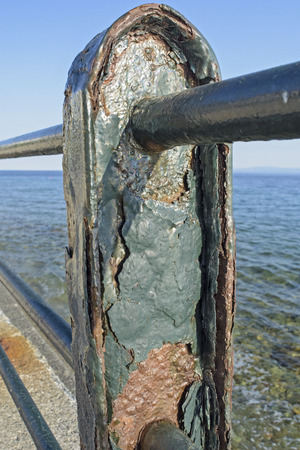 corroded: Corroded metal fence on the sea promenade.
