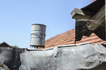 barrel tile: Cobweb on the gutter of the old house.