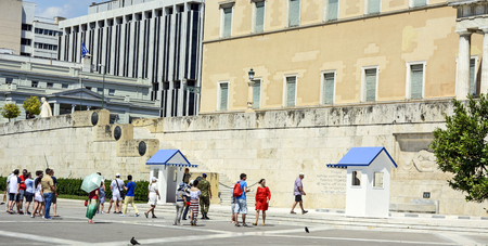 syntagma: ATHENS, Greece - June 04: 2016 Evzones (presidential guards) watches over the monument of the Unknown Soldier in front of the Greek Parliament Building at Syntagma Square on July 04, 2016 in Athens, Greece. Tourists waiting to see the Changing of the Guar Editorial