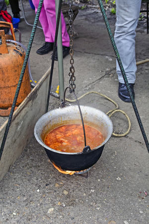 outdoor fireplace: Cooking traditional stew in a kettle outdoors. Stock Photo