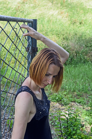 Girl posing behind an old iron gate. Since the fence is only gate remained intact.