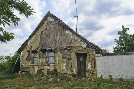 An old abandoned and devastated farmhouse that is prone to decline. Stock Photo