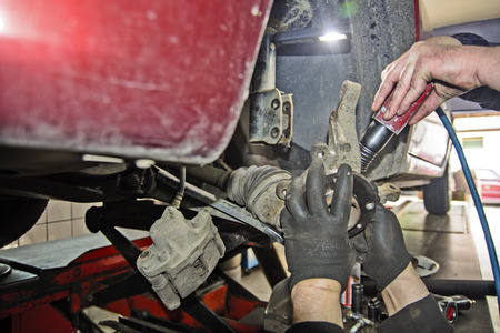 The mechanic in the workshop replaces the bearing on the front axle of the car. Banco de Imagens