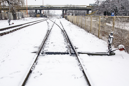 Railroad tracks and crossings at the train station covered by snow.