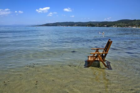 Wooden chairs in the sea water, waiting for the swimmers who will enjoy it.