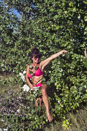 A middle-aged attractive lady in a bathing suit poses in the bushes.
