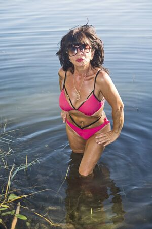 A middle-aged beautiful and tanned lady in a bikini comes out of the water and poses.