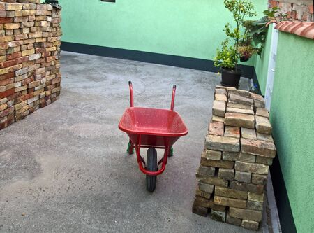 Yard with stacked old brick and red trolley for transport. Only the masons are waiting to start masonry. 写真素材