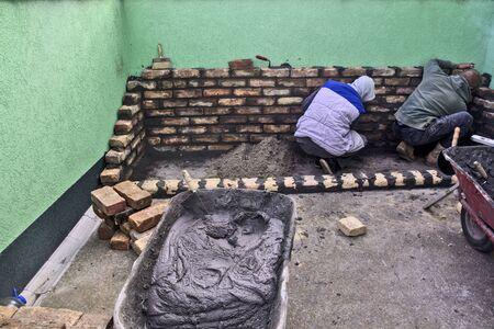 Master masons start masonry and check that it is horizontal.